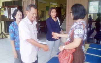 Ibu korban Yesi Krisnatali (baju lengan panjang) bersalaman dengan keluarga yang lain di depan kantor Pengadilan negeri Buntok
