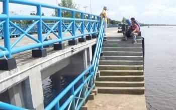 Sejumlah warga sedang duduk bersantai di Dermaga Pelangisan