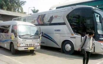 Penumpang berjalan di dekat Bus Damri di Terminal Pangka Raya. Sementara itu, puluhan penumpang Logos kesal mereka dioper di tengah perjalanan ke Bus Damri tujuan Pangkalan Bun dari Banjarmasin.