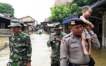 Aparat kepolisian dan TNI mengevakuasi anak kecil dari Desa Sei Hanyo, Kecamatan Kapuas Hulu, Kabupaten Kapuas, yang terendam banjir, Minggu (21/5/2017).