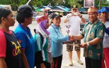 Kepala Dinas Kebudayaan dan Pariwisata Kalteng Guntur Talajan menyerahkan piala kepada pemain habayang putri Gumas yang berhasil juara I, Minggu (25/1/2017).