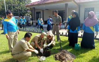 Kepala DLH Sukamara, Rendy Lesmana melakukan aksi penanaman pohon lengkeng di halaman Gedung Gawi Barinjam