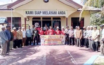 Kapolsek Kapuas Kuala, Iptu Sanip bersama masyarakat foto bersama seusai kegiatan Masyarakat Peduli Api di depan Mako Polsek Kapuas Kuala.