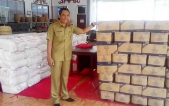 Kepala Dinas Perdagangan Perindustrian Koperasi Usaha Mikro Kecil Kabupaten Kapuas H Suparman saat menujukan barang-barang sembako umtuk pasar murah ynag siap di paketkan