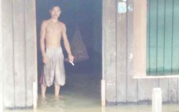 Seorang warga sedang bediri di rumahnya yang sudah dimasuki banjir.