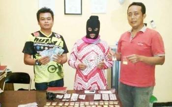 Sulimah (tengah) IRT pengedar 1.221 butir zenith diapit petugas Reserse Narkoba Polres Katingan
