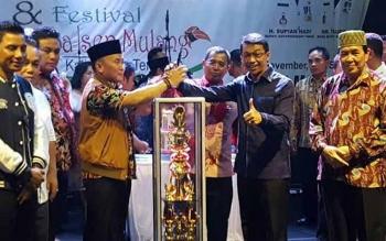 Gubernur Kalteng, Sugianto Sabran menyerahkan piala juara umum FBIM kepada Bupati Murung Raya, Perdie M Yoseph saat malam penutupan yang dilaksanakan di Kota Sampit, Selasa (23/5/2017) malam