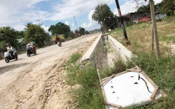 Papan proyek ambruk di pinggir jalan. Lemahnya pengawasan membuat proyek rekonstruksi jalan Bumi Harjo senilai Rp23 miliar ini terkesan asal-asalan.