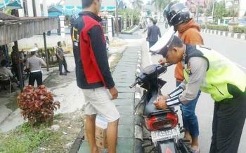 Anggota Satlantas Polres Barut saat melakukan penidakan terhadap pelanggar yang tidak memakai helm saat berkendara.