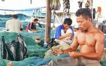 Sejumlah nelayan tengah merajut alat tangkap ikan sebelum dibawa melaut.