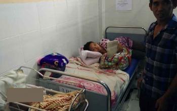 Pasangan Fredi dan Sali bersama anaknya yang mengalami hidrosefalus saat berada di ruang kebidanan RSUD Muara Teweh