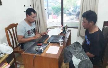 Penyidik Satuan Reserse Narkoba Polres Palangka Raya (kiri) memeriksa Rahman, pengedar narkoba di komplek lokalisasi Km 12, yang ditangkap beberapa hari lalu.
