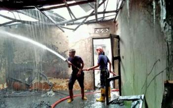 Dua petugas sedang memadamkan api di rumah J Koetin yang terbakar.