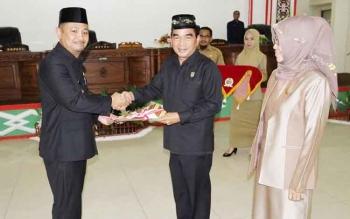 Bupati Barsel, Eddy Raya Samsuri (kiri) menyerahkan raperda tentang PDAM Tirta Barito kepada Ketua DPRD, Tamarzam