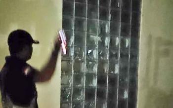 Anggota Satpol PP saat menunjukkan dua bidang kaca di stadion Sampuraga baru yang pecah. Kejadian itu diketahui oleh penjaga stadion pada malam hari.