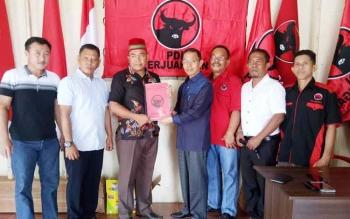 Mugeni saat menyerahkan berkas pendaftaran kepada Sekretaris DPC PDI Perjuangan Sukamara, Jairi.