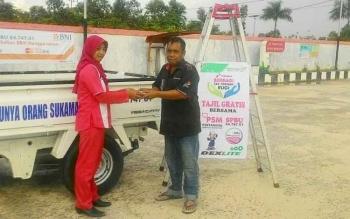 Petugas SPBU PT Bangun Sukma Jaya saat menyerahkan menu takjil kepada pengendara yang usai mengisi bahan bakar minyak (BBM).