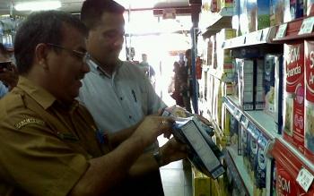Kepala Disperindag Kota Palangka Raya Aratuni D Djaban (kiri) bersama anggota Polres Palangka Raya mengecek tanggal produk di yang dijual di swalayan, Selasa (30/5/2017).