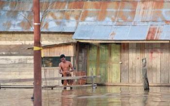 Warga Kelurahan Pangkut Arut Utara berada di dekat rumahnya yang terendam banjir.