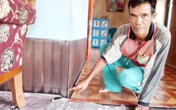 Ibas, warga Desa Sungai Undang, Kecamatan Seruyan Hilir, menunjukkan bekas genangan air sungai Seruyan di lantai rumahnya, Kamis (1/6/2017).