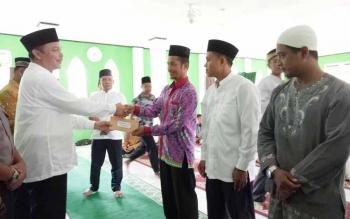 Wakil Bupati Sukamara, Windu Subagio saat menyerahkan bantuan kepada pengurus rumah ibadah.