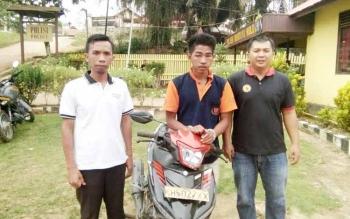 Petugas Polsek Mentaya Hulu sedang mengapit tersangka penggelapan sepeda motor, Yayan.
