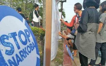 Warga Pangkalan Bun membubuhkan tanda tangan di spanduk stop narkoba