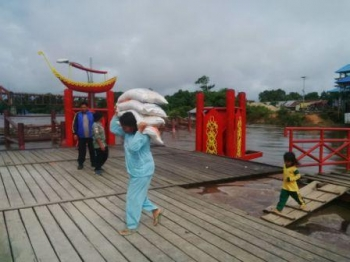 Salah seorang buruh angkut wanita yang bekerja di Pelabuhan Putir Sikan, Kota Puruk Cahu dengan mengangkut beras seberat 60 kilogram untuk mendapatkan upah.