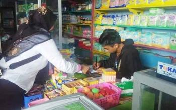Kasir mini market di Kuala Pembuang saat bersama seorang tim gabungan razia makanan dan minuman di Kuala Pembuang, beberapa waktu lalu.