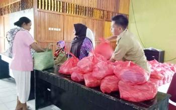 Masyarakat Sukamara saat mengambil paket sembako murah yang disediakan Dinas Koperasi, Usaha Kecil Menengah (UKM) dan Perdagangan Sukamara.