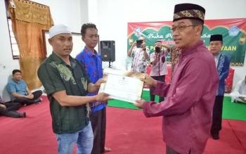 Bupati Mura, Perdie M Yoseph saat memberikan piagam penghargaan kepada warga yang menghibahkan tanahnya untuk membangunkan gedung sekolah, Senin (5/6/2017).