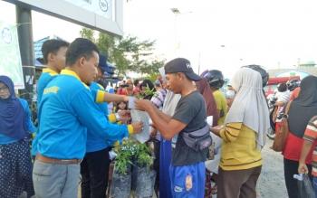 Kepala DLH Sukamara saat membagikan bibit tanaman kepada masyarakat.