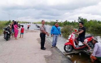 Ruas jalan di Desa Petak Bahandang Kecamatan Tasik Payawan putus karena diterjang banjir.