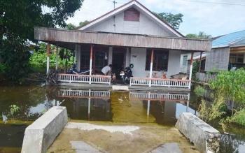 Pekarangan rumah warga mulai terendam banjir di Jalan Kelurahan