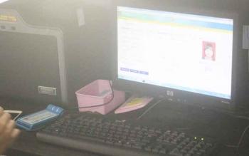 Salah satu petugas Disdukcapil Kabupaten Kotawaringin Barat memeriksa data e-KTP milik warga menggunakan alat pindai.