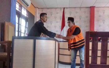 Samsul Arifin terdakwa kasus pembunuhan (pakai peci) saat digiring petugas.