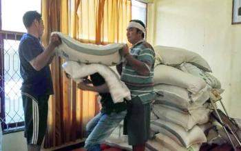 Sejumlah petugas di Bulog sedang mengangkat marug gula pasir yang dibeli oleh warga.