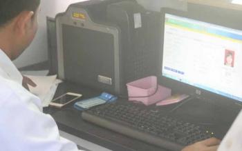 Salah satu petugas Disdukcapil saat memindai e-KTP milik warga untuk memastikan keasliannya.