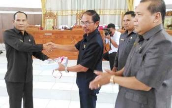 Bupati Gunung Mas Arton S Dohong (kanan) menyerahkan laporan keterangan pertanggungjawaban pelaksanaan APBD 2016 kepada ketua DPRD, Gumer, saat Sidang Paripurna, Rabu (7/6/2017).