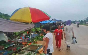 Pedagang Pasar Bahitom pindah ke pinggir jalan saat terjadi banjir di tempat biasa mereka berjualan, beberapa hari lalu.