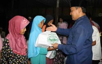 Bupati menyerahkan sembako kepada duafa di Desa Karya Bersama Kecamatan Pandih Batu.