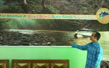 Kepala Seksi Pengelolaan Taman Nasional (SPTN) wilayah II Bikit Baka Bukit Raya Kabupaten Katingan, Firasadi menunjuk spanduk bergambar TN Bukit Baka Bukit Raya, Kamis (8/6/2017)