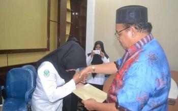 Bupati Sukamara, Ahmad Dirman saat menyerahkan SK kepada salah satu tenaga bidan.