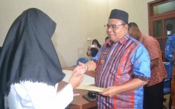 Bupati Sukamara Ahmad Dirman saat menyerahkan SK CPNS kepada bidan.\\r\\n