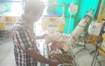 Fredi dengan sabar menjaga anaknya Muhammad Fadil