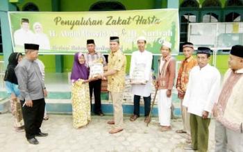 H Hendra Lesmana yang didampingi H Abidin Noor, mewakili keluarga besar H Abdul Rasyid AS, menyerahkan paket sembako zakat kepada masyarakat sekitar Masjid Raudlatul Jannah Nanga Bulik, Jumat (9/6/2017).