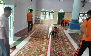 Tampak anggota Polres dan FKUB saat kerja bhakti membersihkan masjid