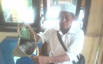 Matbueni (70) saat menunjukan tas berisi uang hasil mengemisnya, di pos satpam Pasar Indra Kencana, Senin (12/6/2017)