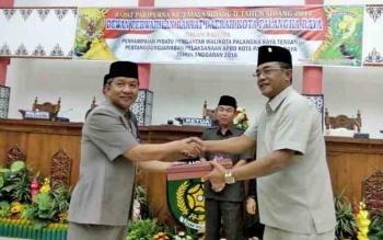 Riban Satia, Wali Kota Palangka Raya menyerahkan dokumen Laporan Pertanggungjawaban Pelaksanaan APBD 2016 kepada Sigit K Yunianto, Ketua DPRD Kota Palangka Raya, Senin (12/6/2017)
