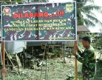 Anggota Koramil Sepang memasang spanduk larangan membakar hutan dan lahan